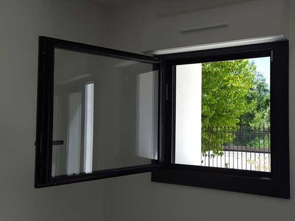 Photo intérieure d'une fenêtre en aluminium gris avec volet roulant