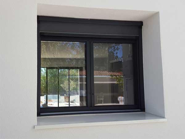 Photo extérieure d'une fenêtre en aluminium gris avec volet roulant